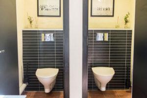 Vägghängda toaletter med fotografier på väggarna.